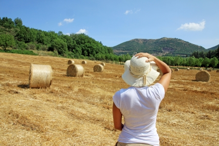 A young girl is looking at a field in Tuscany photo