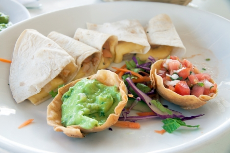 A dish of mexican guacamole with enchiladas photo