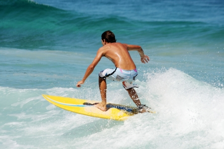 Young guy surfing the wave in a sunny day