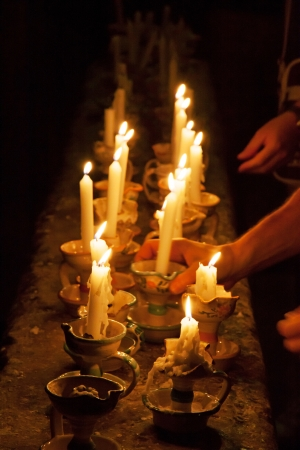 Many candels old style in a dark room photo