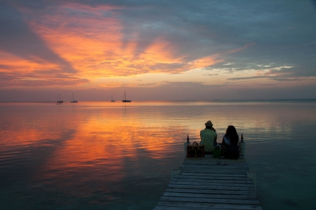 A couple looking at the sunset in Caye Caulker, Belize