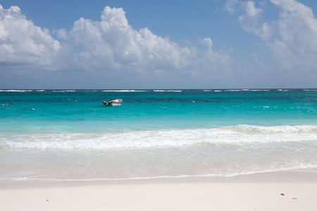 Tulum beach with clear water and a motorboat
