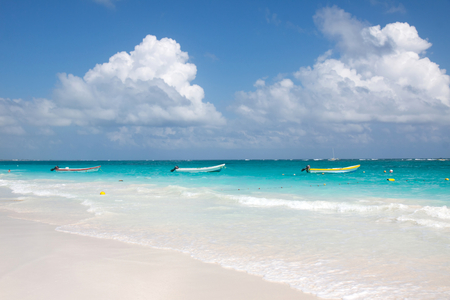 Tulum beach with clear water and a motorboats