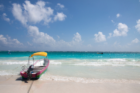 Tulum beach with clear water and a motorboat photo