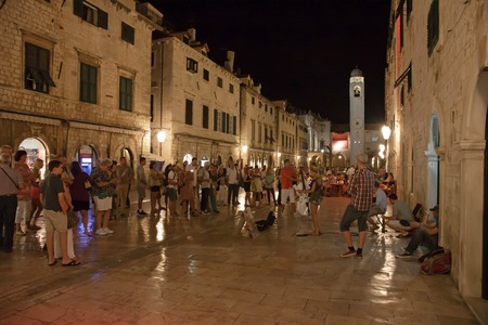 DUBROVNIK, CROATIA - JULY 20, 2013  Tourists walking down at night on Stradun, the main street in the old town of Dubrovnik, running west from Pile Gate to Ploce Gate and the harbor in the east