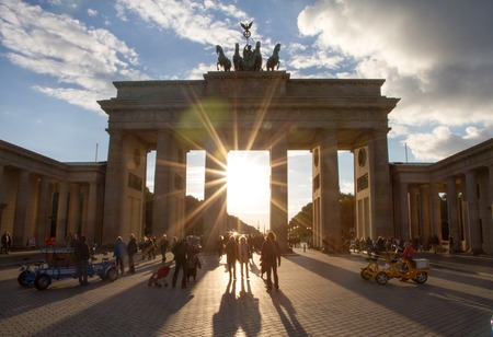 BERLIN, GERMANY - SEPTEMBER 19, 2013 - Tourists in front of Brandenburg Gate in Berlin  It is a former city gate, rebuilt in the late 18th century and now one of the most known landmarks of Berlin