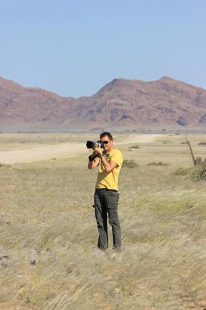 reflex: Fotografo di lavoro all'aperto con una macchina fotografica reflex