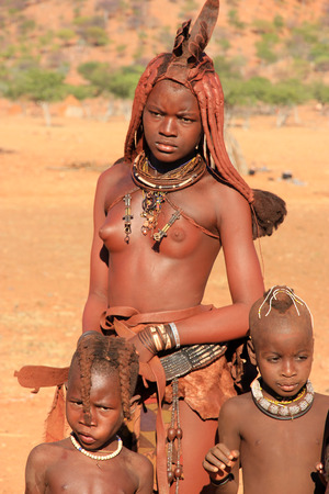 EPUPA, NAMIBIA- MAY 12, 2014: Portrait of an unidentified Himba woman with two children The Himba are indigenous peoples living in northern Namibia, in the Kunene region of South-West Africa