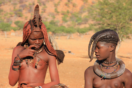 EPUPA, NAMIBIA- MAY 12, 2014: Portrait of two unidentified Himba  young woman with two children The Himba are indigenous peoples living in northern Namibia, in the Kunene region of South-West Africa Editorial