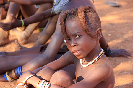 EPUPA, NAMIBIA- MAY 12, 2014: Unidentified child Himba tribe. Himba children show their traditional clothing, jewelry and headdress. The age and social status of a Himba can be seen in their hairstyle and jewelry.
