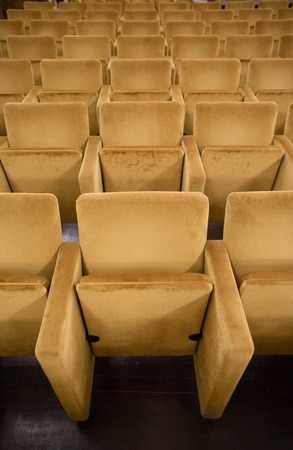 internships: Empty chairs at cinema or theater with golden Tone