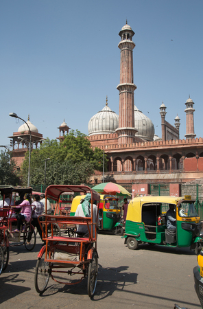 tuk tuk: OLD DELHI, INDIA - October 10, 2015: Overcrowded street in old town with smog, tuk tuk,  cycle rickshaws transports passenger and Jama masjid mosque in the background Editorial