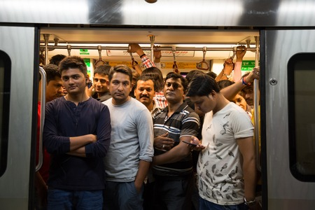crowded: NEW DELHI, INDIA - OCTOBER 11, 2015: Crowd of people in the subway train in  in the  rush hour. They are waithing the door closing and the train departure. Editorial