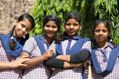 school uniforms: DELHI, INDIA - OCTOBER 11, 2015: unidentified local school girls for tour in Qutub Minar complex in Delhi, India. The girls  in school uniform have fun posing for a foto. Schools visit the famous landmarks as part of national education.