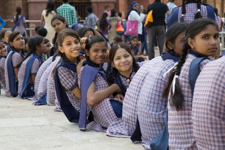 DELHI, INDIA - OCTOBER 11, 2015: unidentified local school girls for tour in Qutub Minar complex in Delhi, India. The girls  in school uniform have fun posing for a foto. Schools visit the famous landmarks as part of national education.