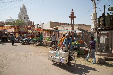 bikaner: BIKANER, INDIA - OCTOBER 12, 2015: A every day view of a typical street in the old market of Bikaner, India, with people selling fruits and vegetables, women with colorful saris and people carrying their belongings