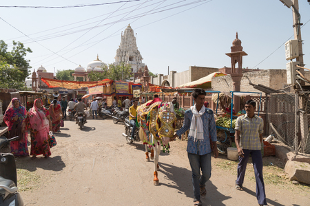 decorated bike: BIKANER, INDIA - OCTOBER 12, 2015: A every day view of a typical street in the old market of Bikaner, India, with people selling fruits and vegetables, women with colorful saris people carrying their belongings