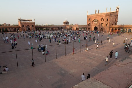 prayer tower: JAMA MASJID, DELHI, INDIA - OCTOBER 11, 2015: It is the largest mosques in India with people entering. The mausoleum is visited by thousands of Muslims people every week. The courtyard can accommodate more than 25,000 persons.