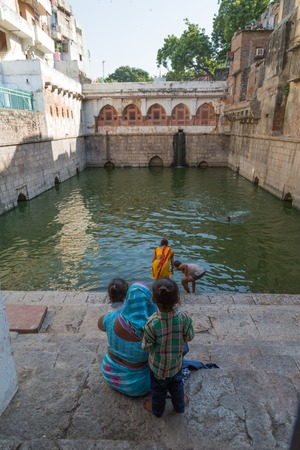 purifying: NIZAMUDDIN DARGAH, DELHI, INDIA - OCTOBER 10, 2015: The pool inside the mausoleum. Moving water and bathing is considered purifying in Hindu culture because it is thought to both absorb impurities and take them away.