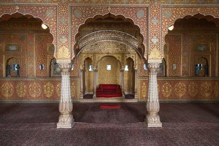 trono: BIKANER, INDIA - 12 de octubre, 2015: sala de descanso del Maharajá con arcos en los patrones de oro dentro Junagarh siglo 16. Se llama una paradoja entre la arquitectura militar medieval y bonita decoración de interiores