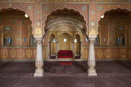 old interior: BIKANER, INDIA - OCTOBER 12, 2015: Maharajas resting room with arches in gold patterns inside 16th century Junagarh Fort. It is called �a paradox between medieval military architecture and beautiful interior decoration�