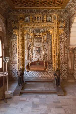 bikaner: BIKANER, INDIA - OCTOBER 12, 2015: Maharajas rocking chair in the interior of  16th century Junagarh Fort. It is called �a paradox between medieval military architecture and beautiful interior decoration�