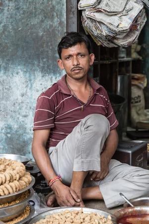 bikaner: BIKANER, INDIA - 0CTOBER 12, 2015: Indian male vendor sitting outside of his shop in the old market of Bikaner