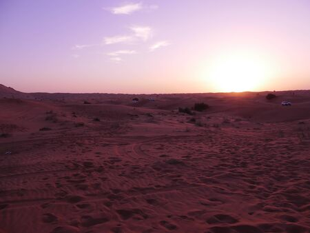 Violet sunset with clouds in the desert and safari cars Imagens