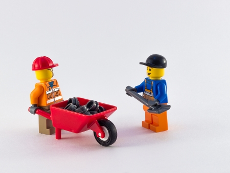 pushcart: two toy workers witn pushcart and shovel on the white