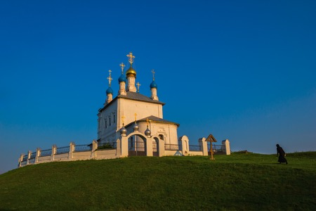 Black dressed nun walking to old white russian christian church on top of green hill, covered by short green grass.