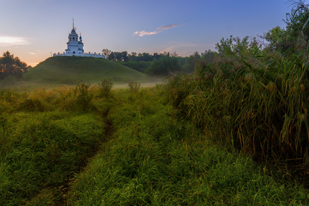 foggy hill: Russian christian church on hill foggy morning swamp landscape
