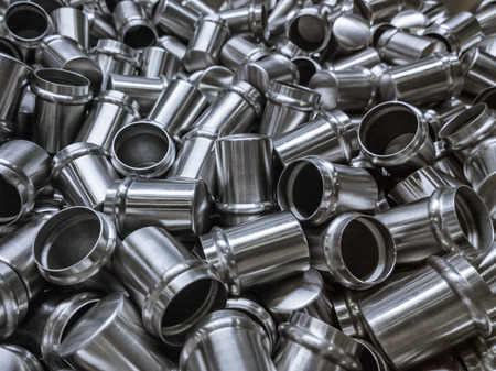 body parts: Shiny cold deformated cylindrical steel body parts selective focus  background Stock Photo