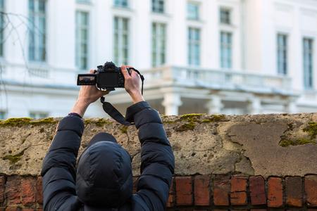 Hombre disparando por encima de la valla Foto de archivo - 77896965