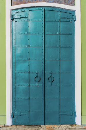 fresh painted old riveted iron double door with two rings