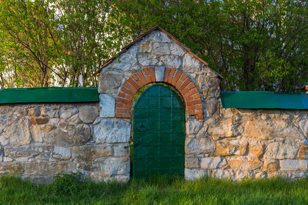 limestone fence with iron riveted wicket at spring evenoing Stock Photo