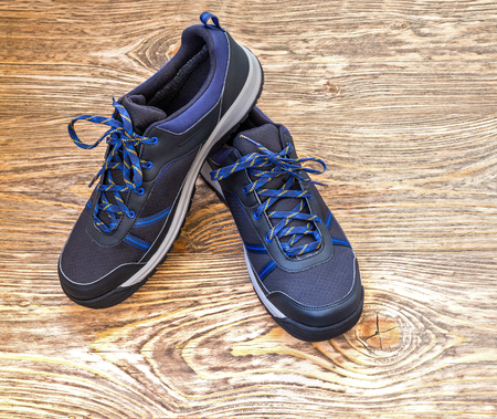 black outdoor sneakers on wooden surface
