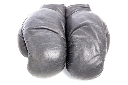old black leather boxing gloves isolated on white background with shadows lying on flat surface