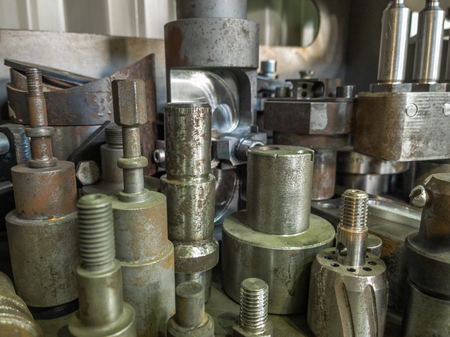 A lot of old rusted machining stock holders dark industrial background with selective focus.