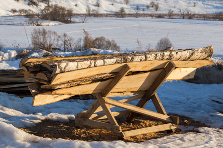firewood lumber leftovers on trestle at winter evening with selective focus Stock Photo