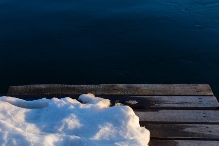 wooden pier with snow on dark water background