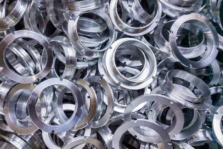 a batch of machined shiny aluminium parts with selective focus