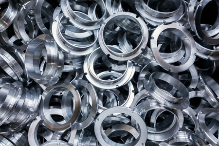 a batch of machined shiny metal parts with selective focus