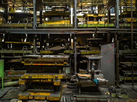 messy stamping shop with large stamps rack inside metalworking factory