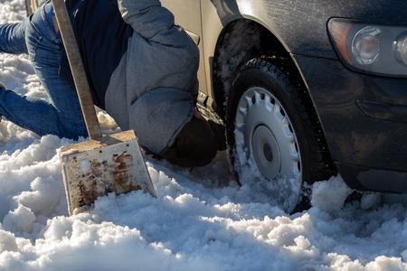 L'homme travaillant à la voiture coincé dans la neige sur le genou avec une pelle à la lumière du jour tout-terrain Banque d'images