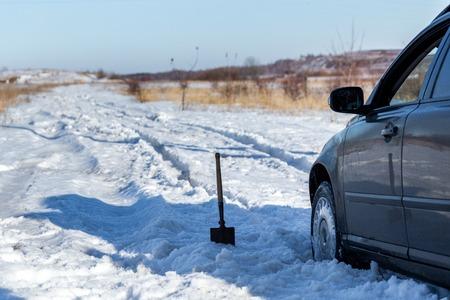 voiture coincée dans la neige hors route à la lumière du jour avec pelle et mise au point sélective