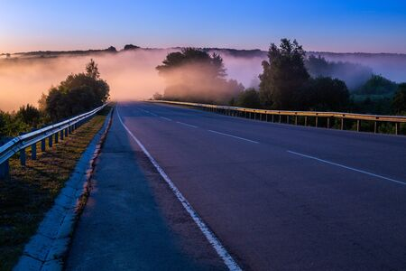 dence early morning fog in wold at summer highway near river with guard rails