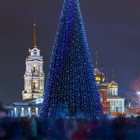 Christmas tree at night in central city square with crowd blurred by long exposure. Tula, Russia, 2018