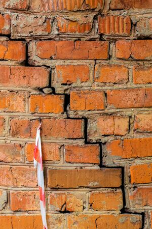 Deep cracked orange brick wall closeup texture and background. Vertical shot. Imagens