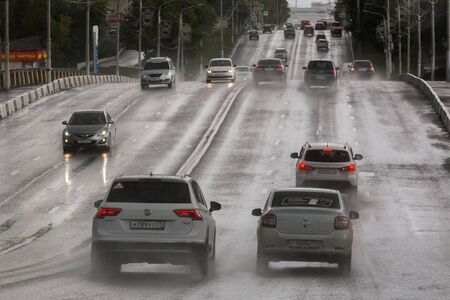 TULA, RUSSIA - JULY 6, 2019: Cars on summer hilly road moving after rain.