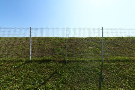 Metal wire industrial grid fence on green grass with blue sky background wide angle shot.